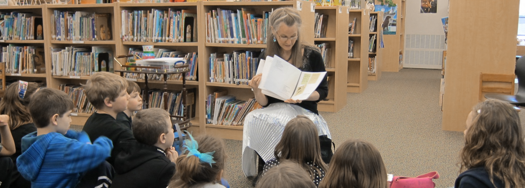 Debra Fraser reads to children in school library